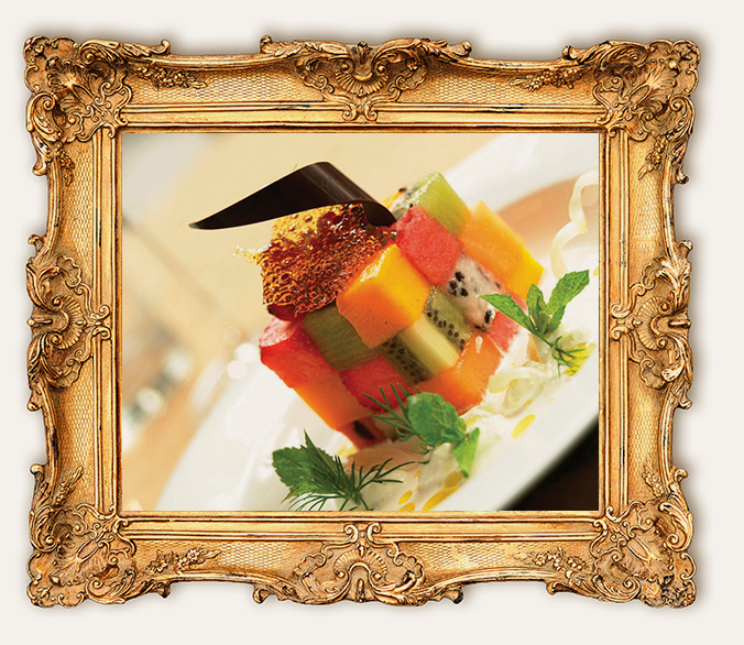 Cube of fruit on plate in gold frame