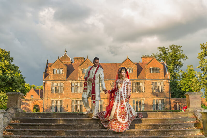 Asian wedding couple in front of house