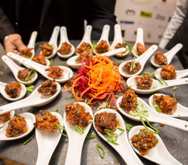 Indian bhajis on white spoons around table