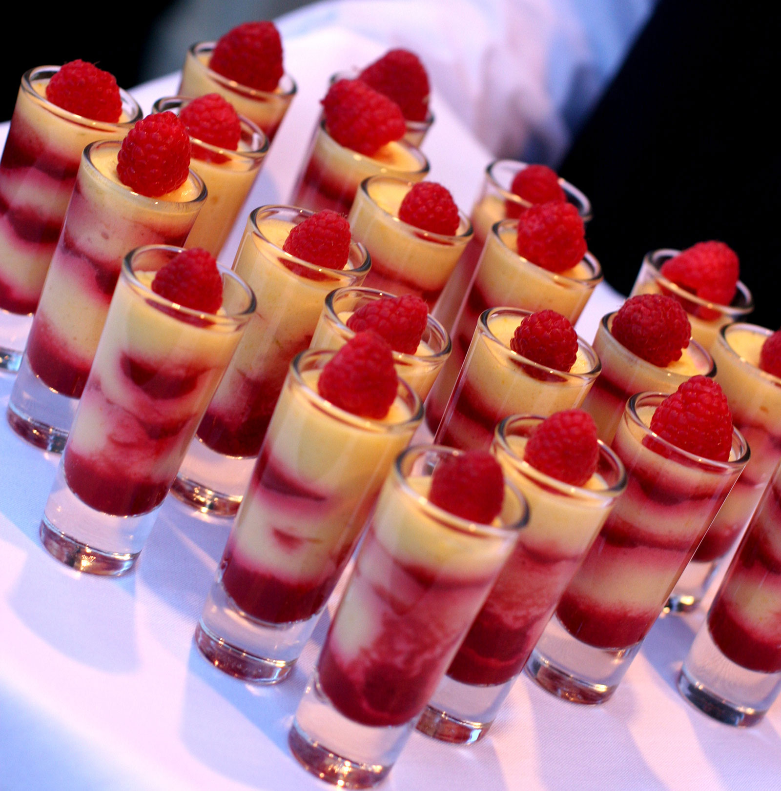 Multiple raspberry and cream desserts in glasses with raspberry on top